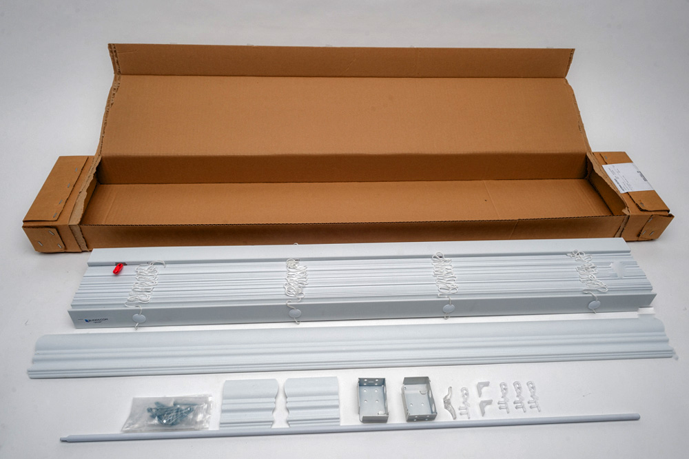 Faux wood blinds neatly placed next to it's open box and displaying all included brackets, hardware and screws.