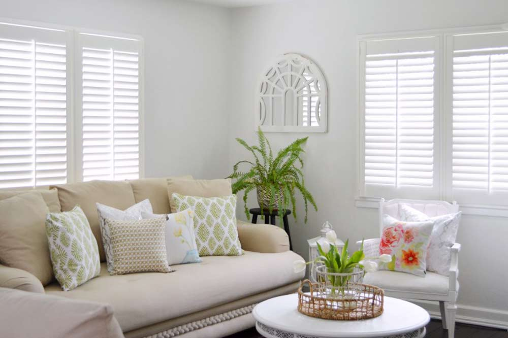 Light and Airy living room with white Composite Shutters installed over the windows behind a contemporary beige couch and white arm chair.
