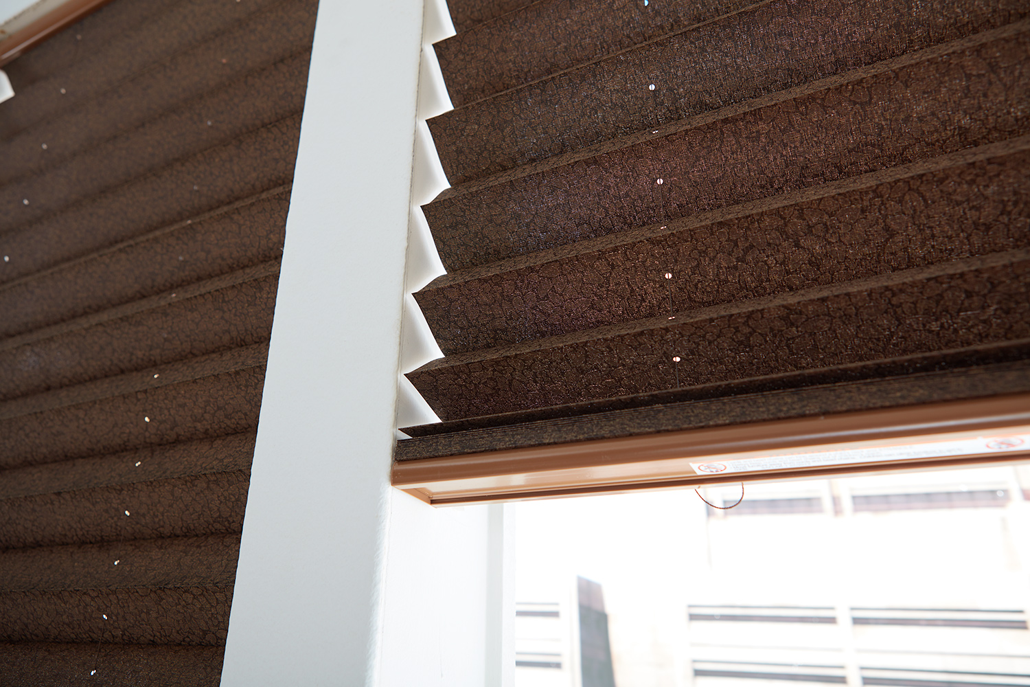 closeup of brown fabric pleated shades