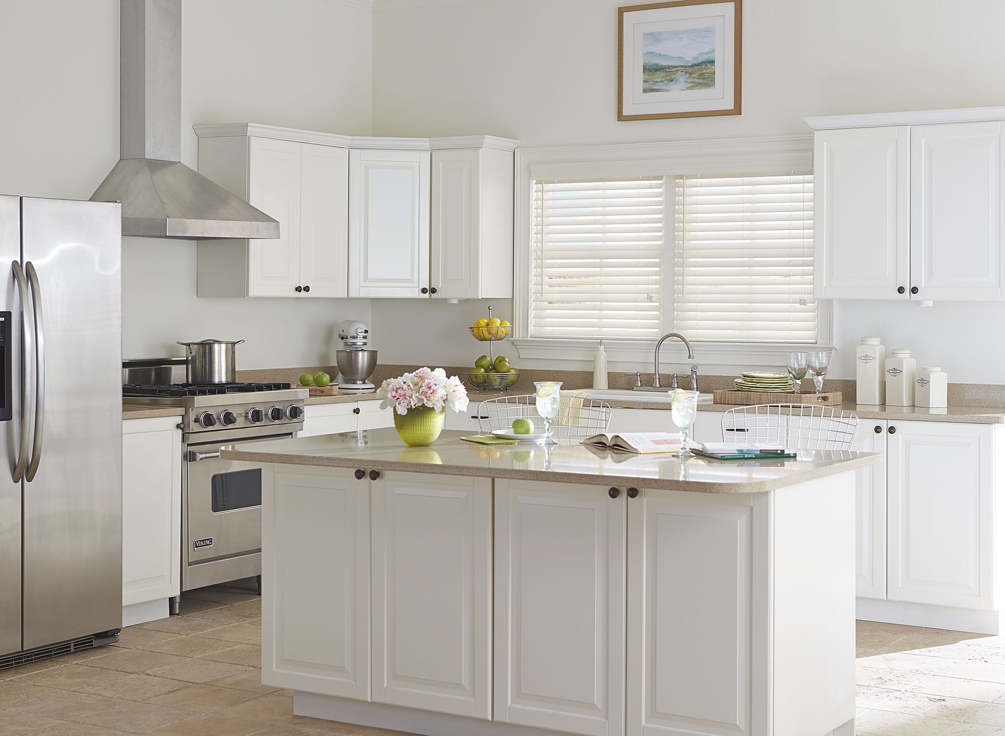 Bright, contemporary kitchen with white walls, white cabinets and white window blinds.