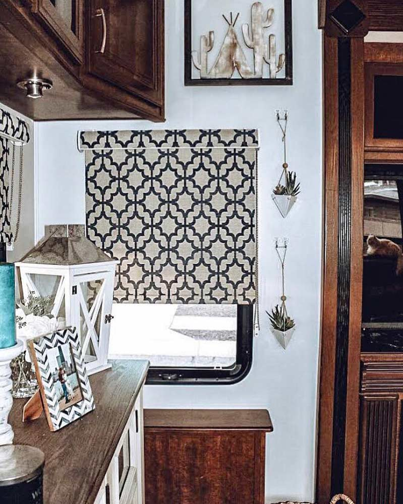 A close up of Tiny Home Hailey's navy blue and beige, trellis pattern roller shades in her RV.
