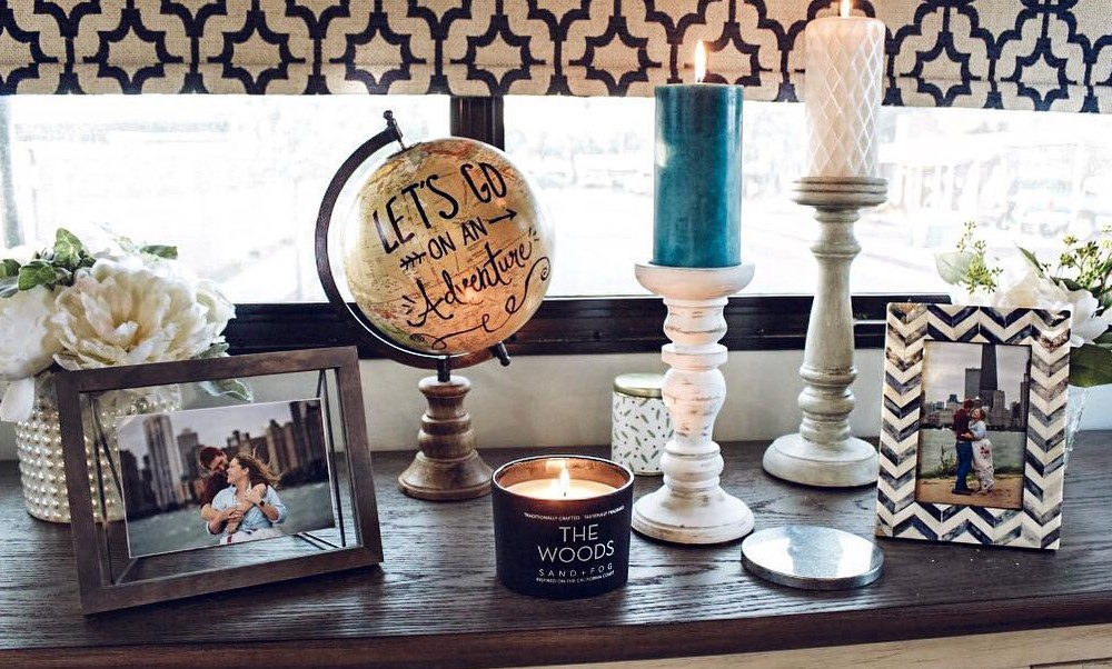 Rustic candles, vases and picture frames with photos of Tiny Home Hailey and Michael on a dark wood display cabinet.