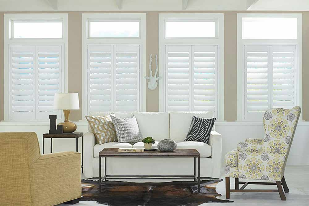 A bright, contemporary living room with four tall windows and Woodcore Faux Wood Shutters installed in color White.