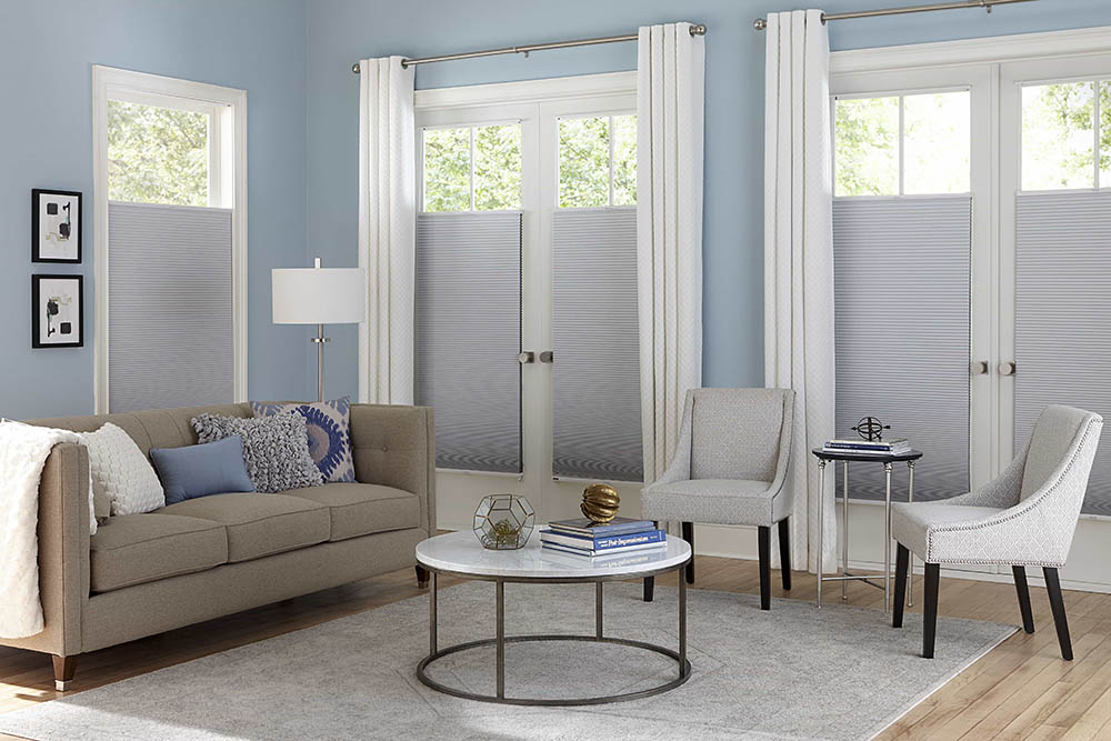 Contemporary blue and beige living room with white, top-down bottom-up cellular shades over the windows and french doors.