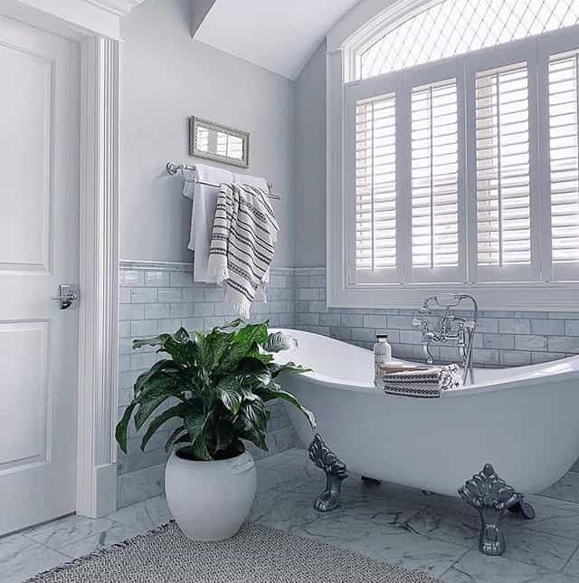 Traditional bathroom with clawfoot tub and white shutters in the arch window.