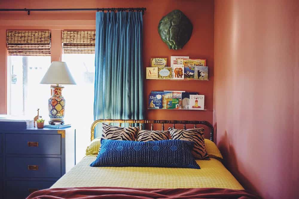 Yellow bed pushed into a corner with terra cotta colored walls, contrasting blue drapes and woven wood shades on the window. Children's books mounted on a shelf above the bed.
