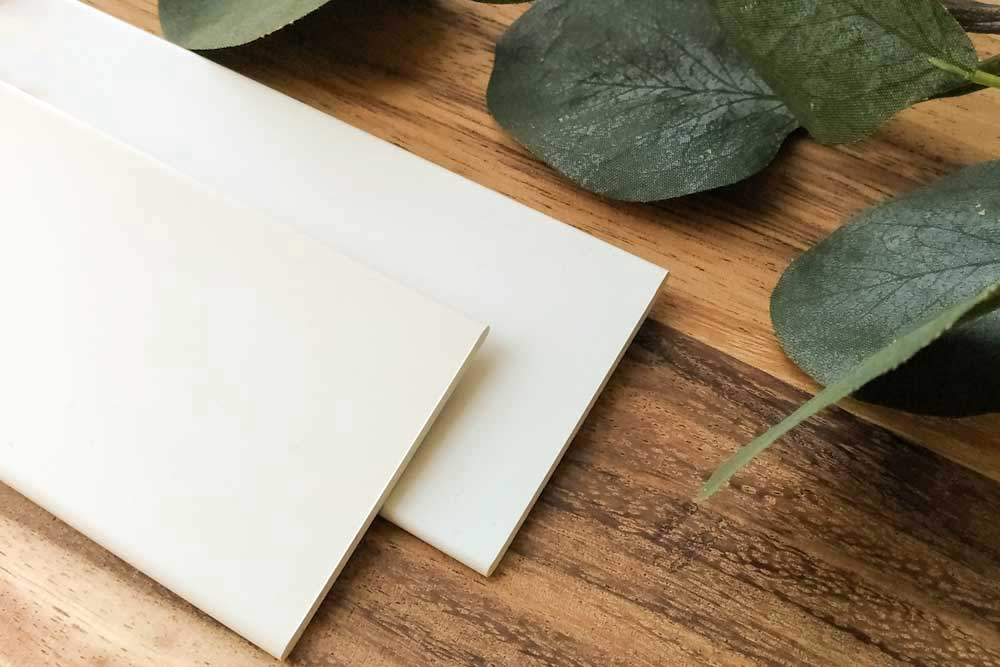 A closeup of the faux wood blind colors white and off white on a wood table with foliage.
