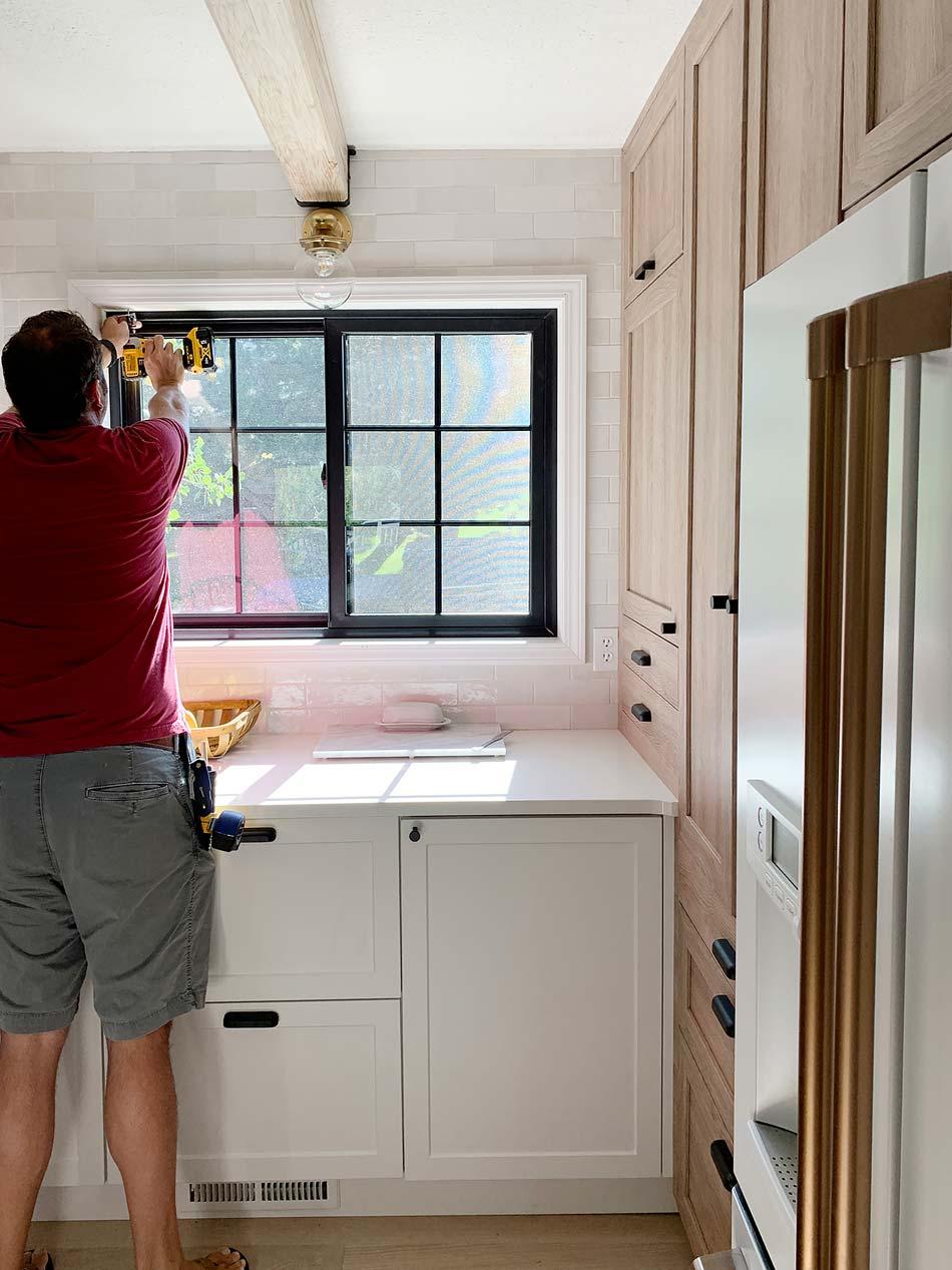 man installing window shades in kitchen