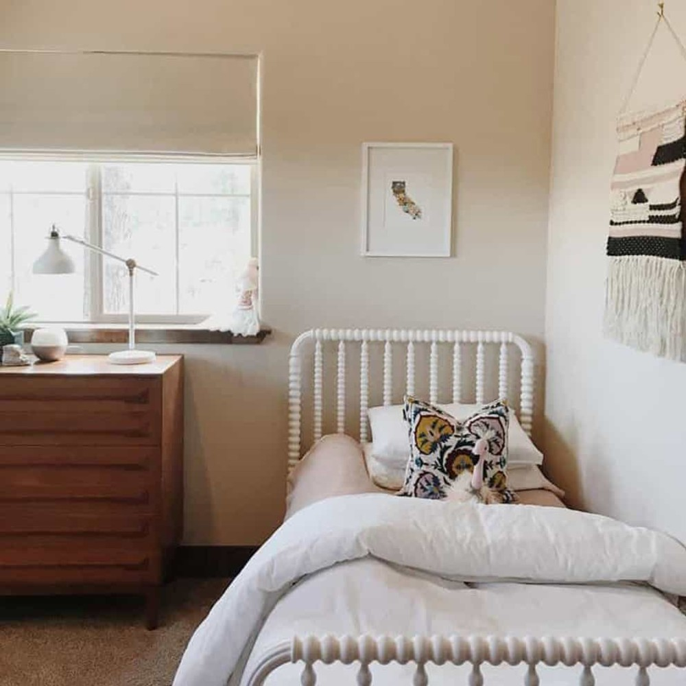 Girl's room with neutral pink and white bedding, wall tapestry, and off white roman shades in the window.