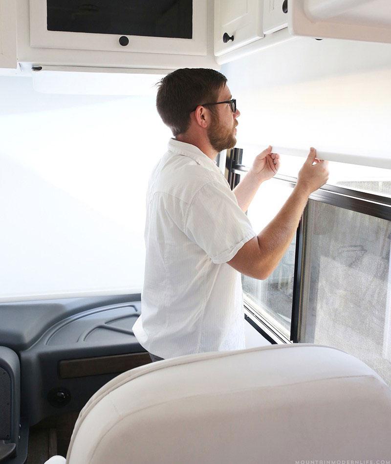 man lowering window shades in RV cab