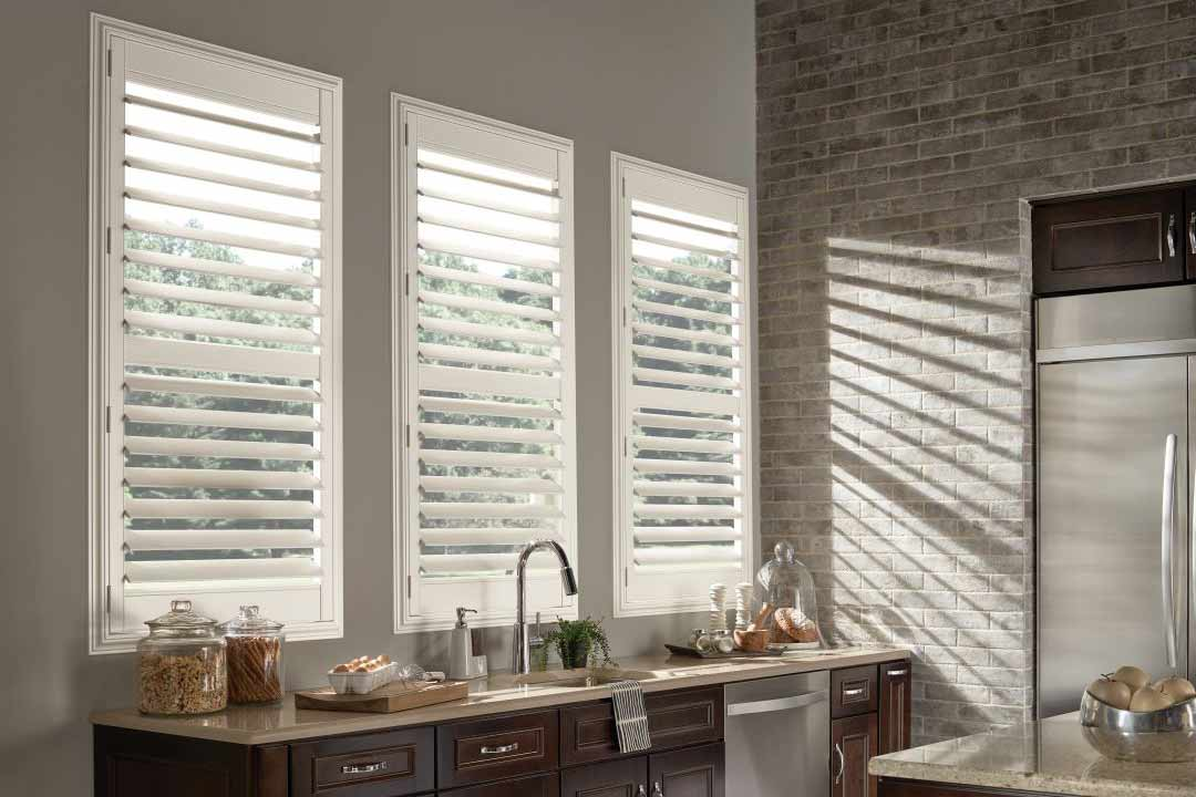 Tall window over a contemporary kitchen sink counter. Levolor Traditional Shutters in the color white are installed in the windows.