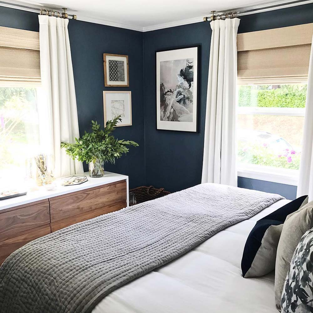 small bedroom with navy walls, woven window shades and white curtains