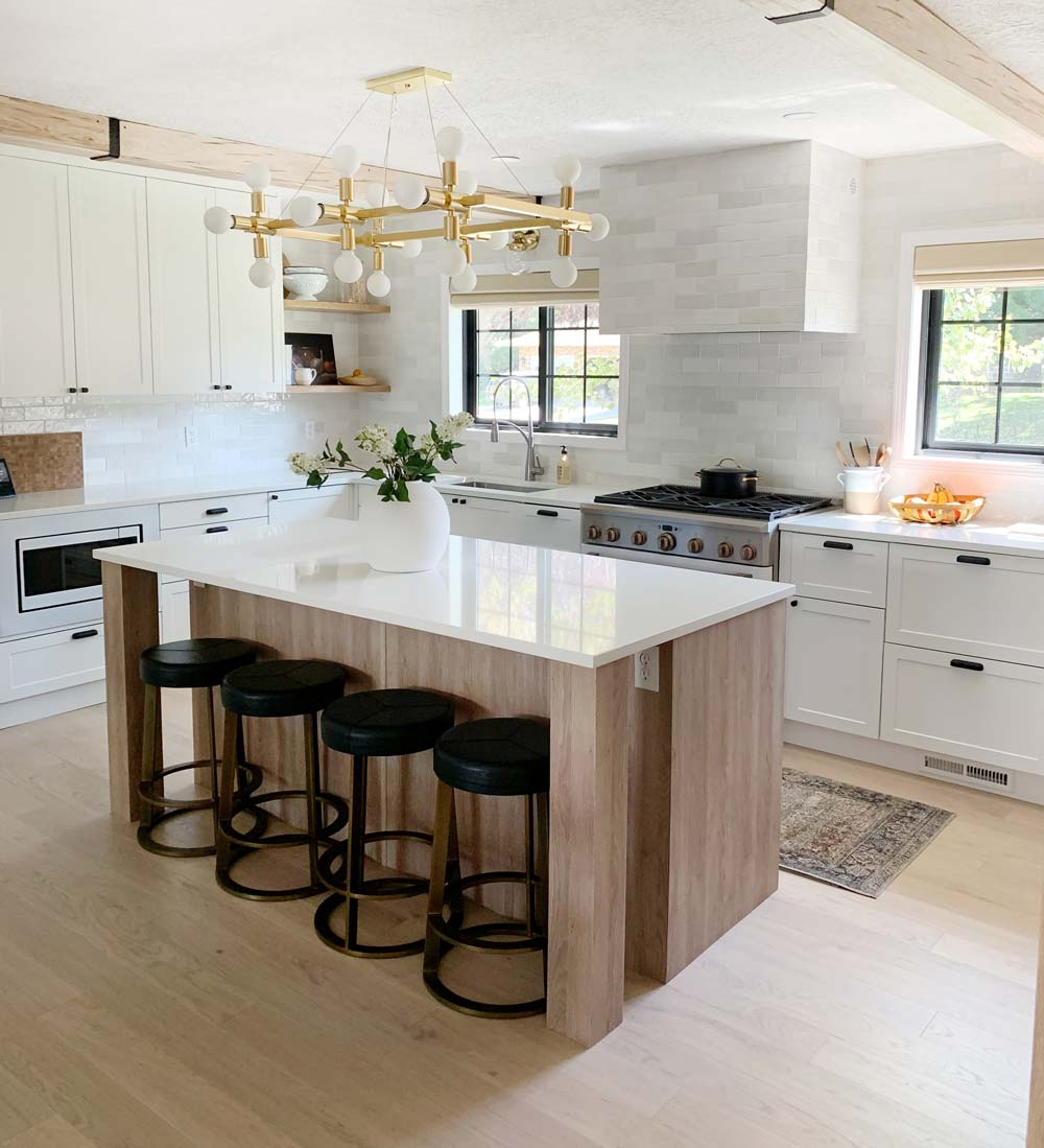 white kitchen with wood island and brass light fixture