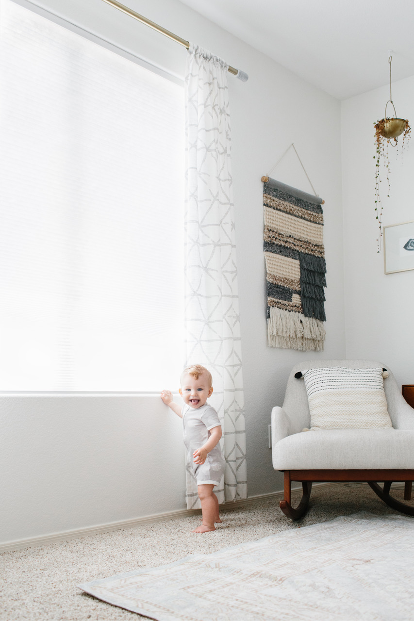 Baby Ezra standing near a nursery window with light filtering cellular shades.
