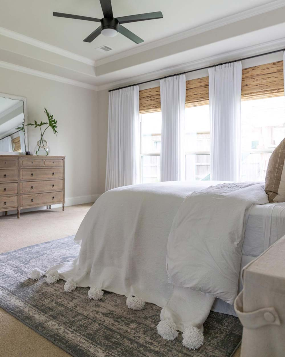 neutral master bedroom with beige walls, white curtains and bamboo blinds