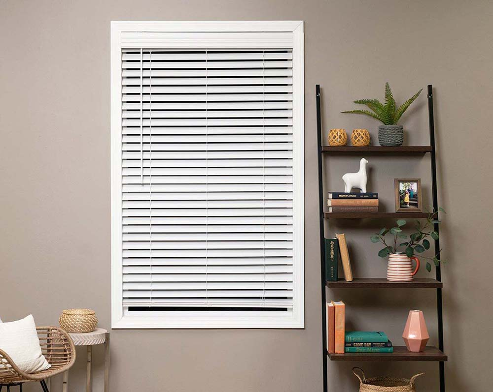 A living room window with the Blinds.com Economy Cordless Faux Wood Blind installed in the bright white.