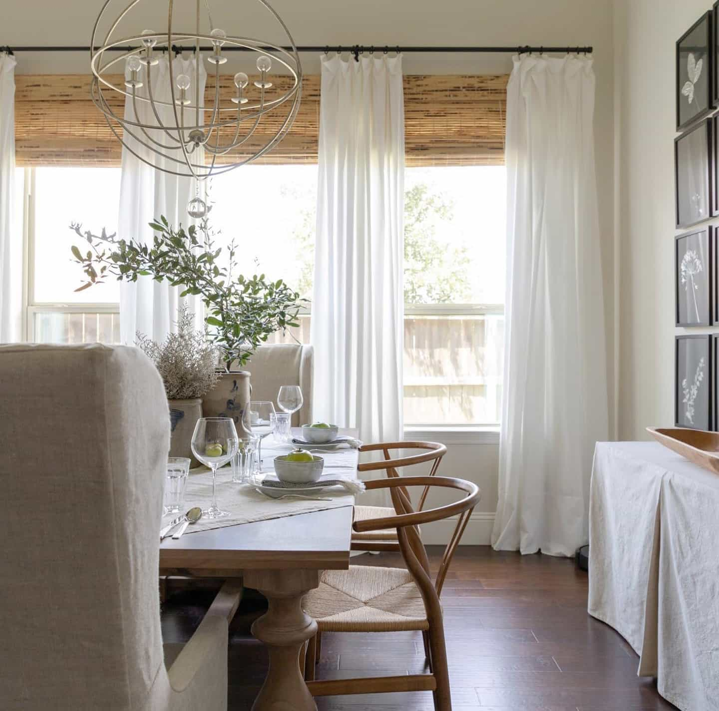 Modern farmhouse dining room with woven wood shades and white drapes over the windows.