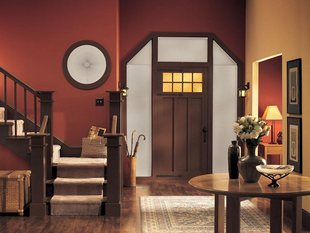 Traditional home entryway with angle top sidelight windows around the front door and a circle window over the stairs. Specialty shape cellular shades are installed in tall the windows.