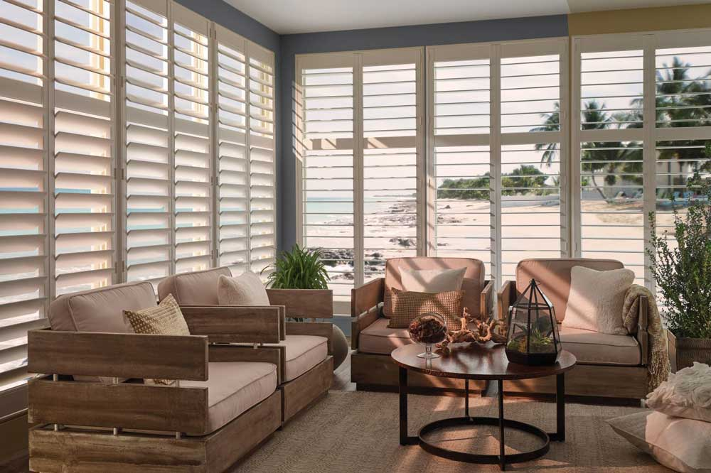 Beachy living room overlooking the water will walls of windows and white Levolor Traditional Shutters installed with slats tilted open.